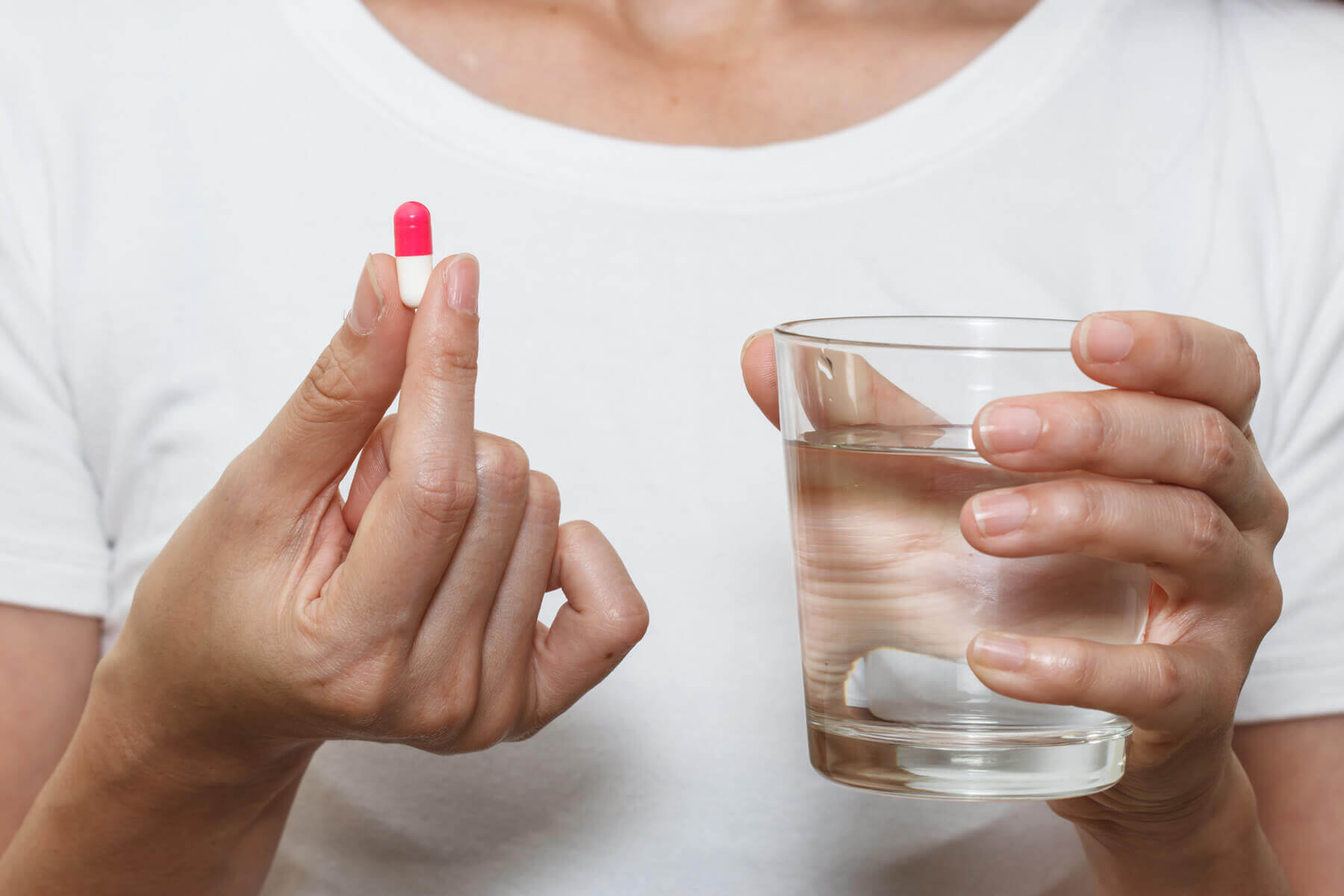 hands holding capsule pill and a glass of water
