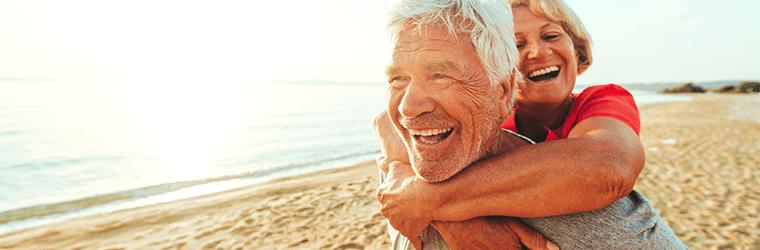 Glückliches älteres Paar am Strand